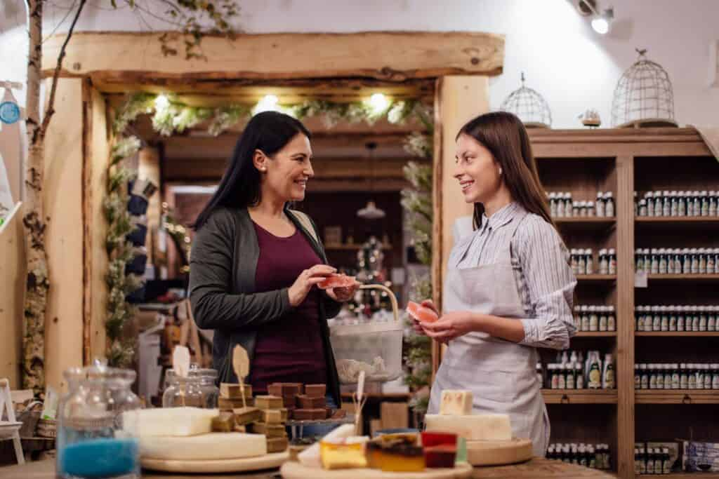 Cheerful shopkeeper helping customer